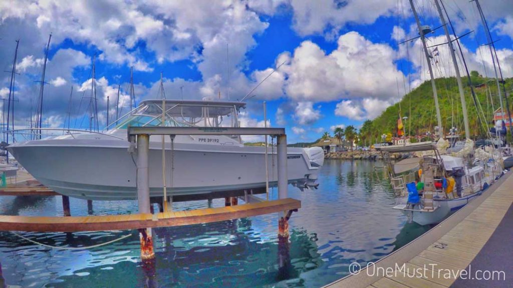 A white boat in a dry dock over the water at the marina in Marigot St. Martin. There is a blue sky with fluffy white clouds and a green mountain in the background.
