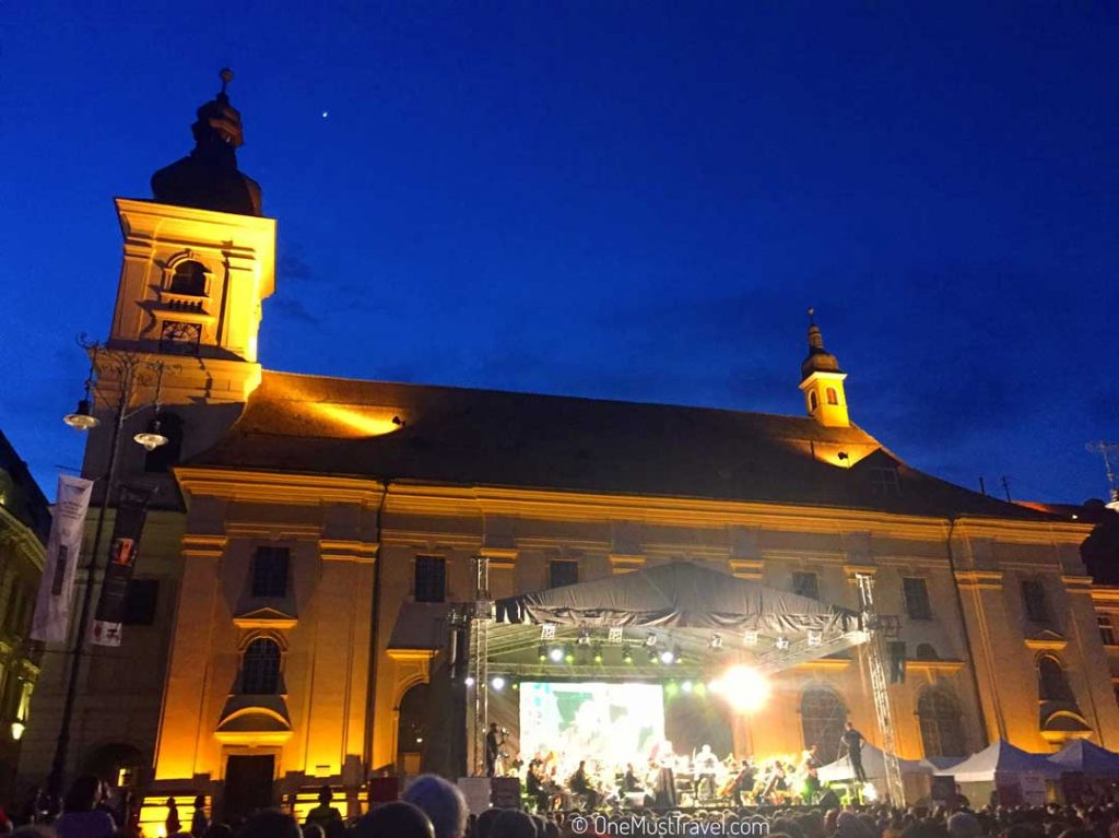 A concert lit up at night in front of a historic building in Sibiu.