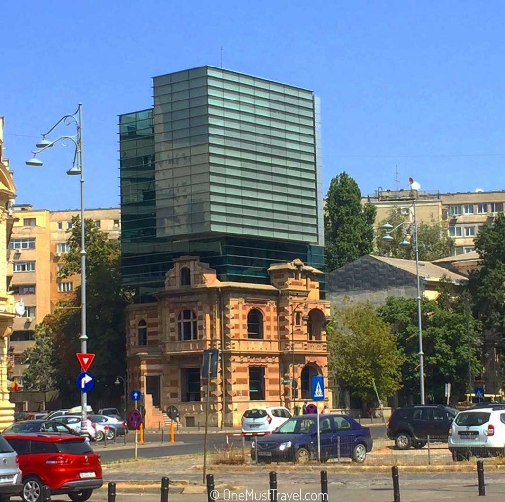 A building in Bucharest that is old looking on the bottom and modern looking on the top.