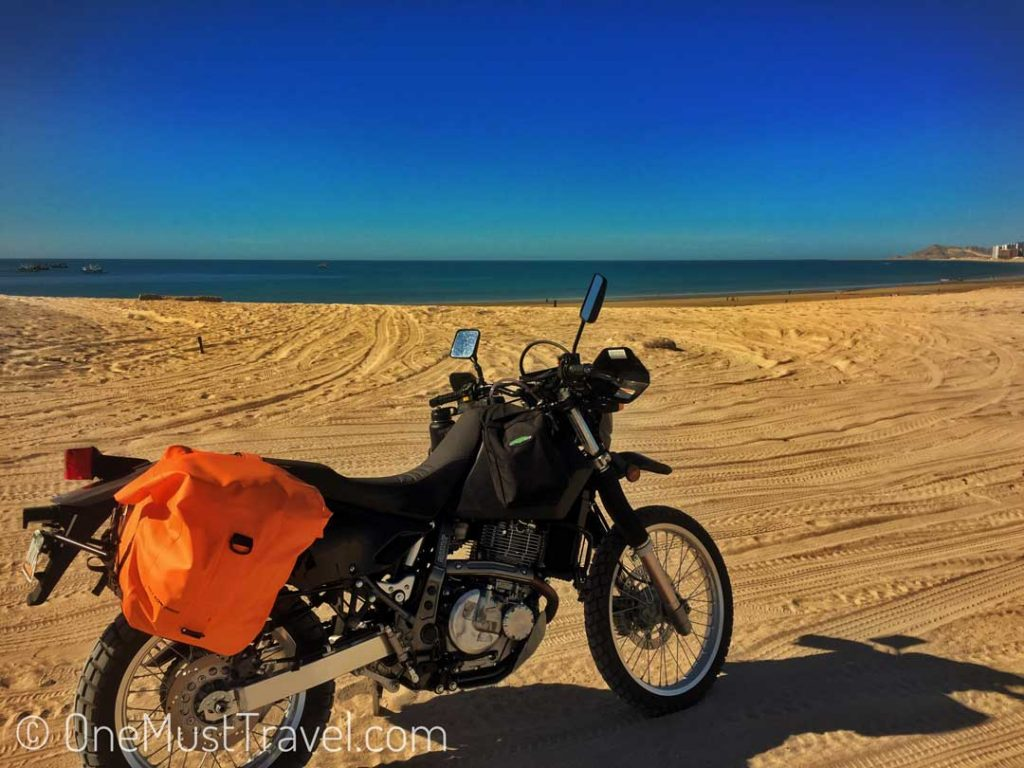 A picture of a dual sport motorcycle (Suzuki Dr650) on the beach in Mexico. The sky is blue and the ocean looks inviting.