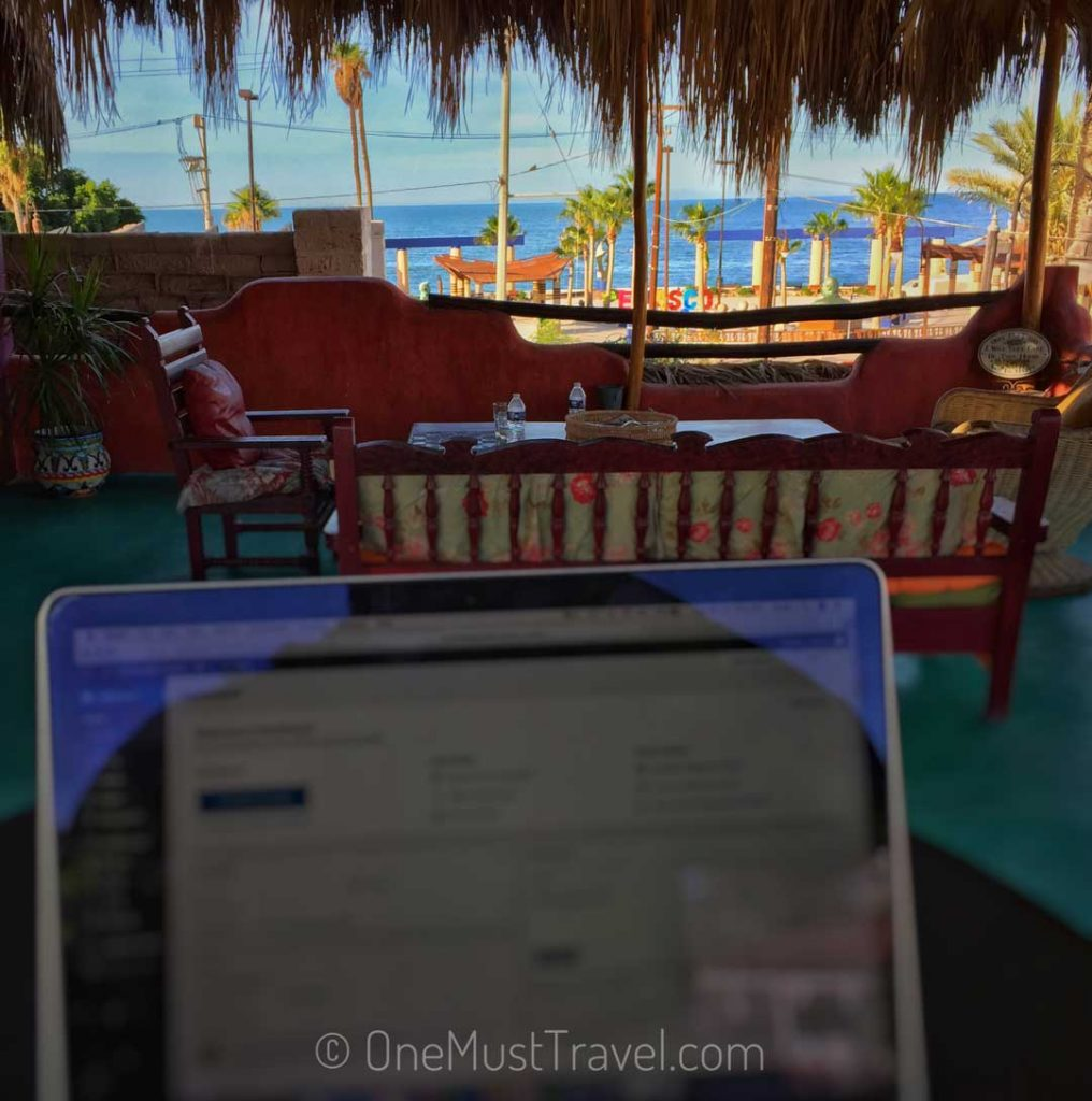 View of me working on my laptop with a great view of the ocean.