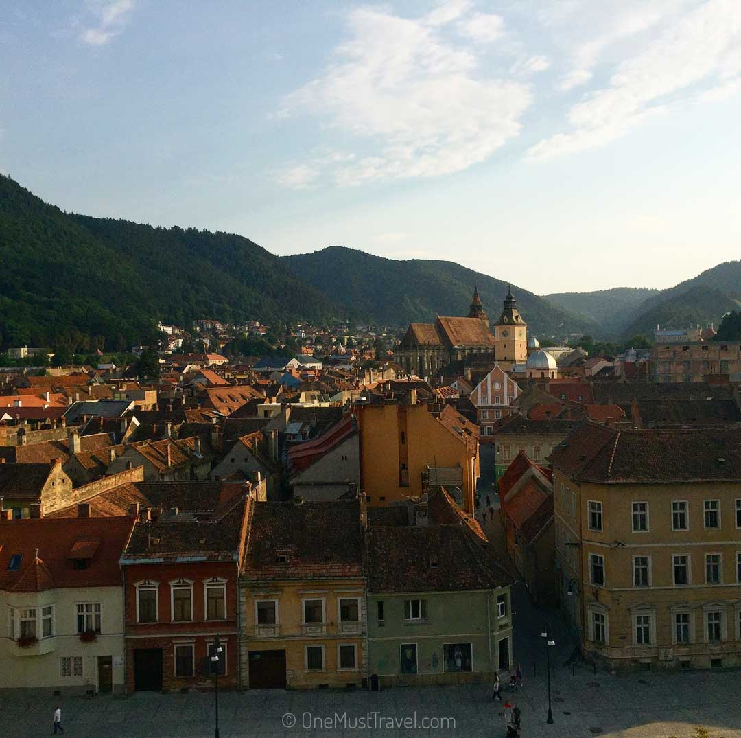 A view from a hotel room high above the historical part of brasov. The view is looking out from the Hotel Aro Palace. There is a small hill lush with greenery. The old city center is made up of medieval looking buildings.